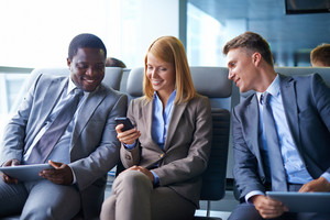 Smiling Young Woman With Cellphone Sitting In Airport With Two Male Colleagues Near By