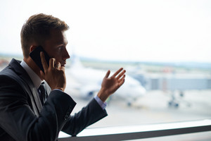 Elegant Businessman Speaking On Cellular Phone In Airport