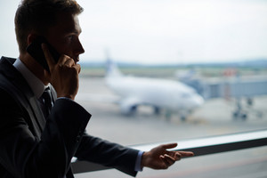 Serious Businessman Talking On Cellular Phone In Airport