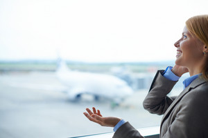 Charming Businesswoman Speaking On Cellular Phone In Airport