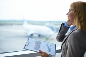 Charming Manager With Document Speaking On Cellular Phone In Airport