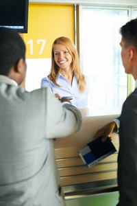 Smiling Female Returning Documents To Businessman At Airport Check-in Counter
