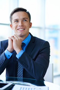 Cheerful Businessman Sitting At Workplace In Office