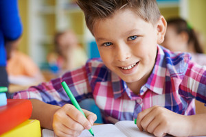 Portrait Of A Cute Schoolboy Looking At Camera While Drawing At Lesson