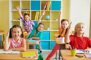 Portrait Of Little Classmates Raising Hands At Lesson