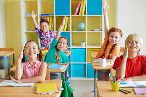 Happy Classmates Raising Hands At Lesson