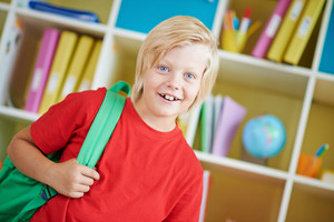 Portrait Of A Cute Schoolboy With Backpack Looking At Camera