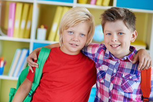Portrait Of Two School Friends With Backpacks Looking At Camera