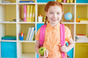 Portrait Of A Lovely Girl With Backpack And Green Apple Looking At Camera