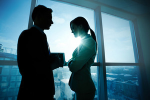 Two Business Partners Standing By The Window In Office And Interacting