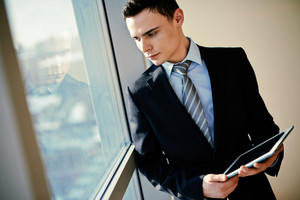 Serious Young Businessman With Touchpad Looking Through Window