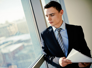 Serious Young Businessman With Papers Looking Through Window