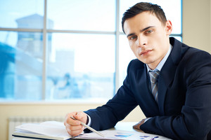 Serious Young Businessman Looking At Camera At Workplace