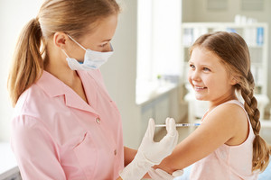 Adorable Girl Looking At Nurse While She Making Her An Injection In Clinics