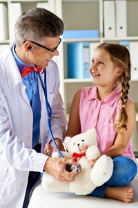 Joyful Girl Looking At Her Doctor Examining Teddy Bear In Hospital