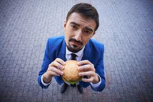 Image Of Hungry Businessman With Sandwich Looking At Camera Outside