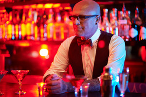 Bald Male In Eyeglasses Waiting For Clients In The Bar
