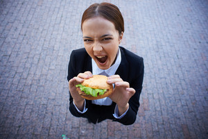 Image Of Very Hungry Businesswoman With Sandwich Looking At Camera Outside