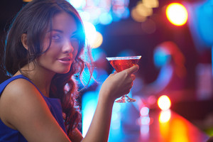 Pretty Young Girl With Martini Looking At Camera In The Bar