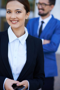 Image Of Pretty Businesswoman With Cellphone Looking At Camera On Background Of Her Co-worker