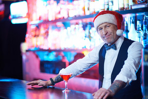 Serious Man In Santa Cap Looking At Camera In The Bar