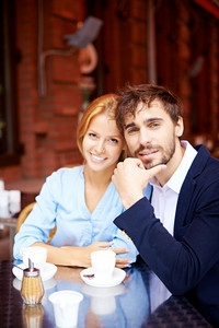 Portrait Of Affectionate Couple Looking At Camera In Cafe