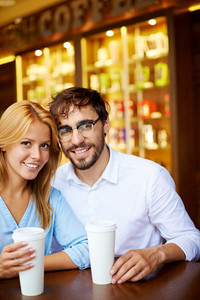 Portrait Of Young Couple Looking At Camera In Cafe