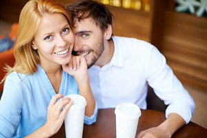 Portrait Of Young Couple Sitting By Table In Cafe