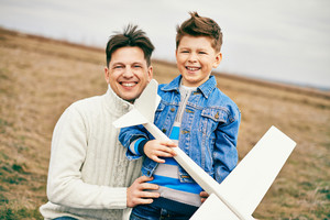 Photo Of Happy Boy With Toy Airplane And His Father Looking At Camera Outdoors