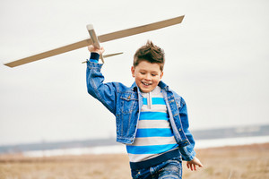Photo Of Happy Kid Playing With Toy Airplane Outside