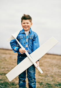 Photo Of Happy Kid With Toy Airplane Looking At Camera Outside