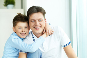 Photo Of Happy Man And His Son Looking At Camera With Smiles While Boy Embracing His Father