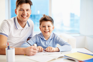 Photo Of Happy Man And His Son Sitting By Table And Looking At Camera