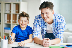 Photo Of Happy Man And His Son Looking At Camera At Home