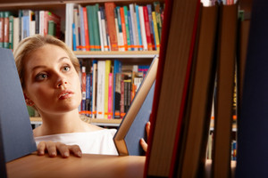 Portrait Of Clever Student Looking For A Book In College Library