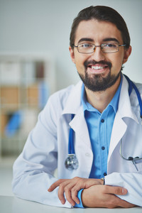 Portrait Of Smiling Male Doctor Looking At Camera At Workplace