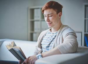 Portrait Of Young Guy In Casual Clothes Reading Book