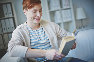 Portrait Of Young Guy In Casual Clothes Reading Book At Home