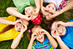 Group Of Cute Children Lying On Grass