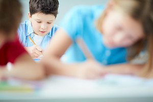 Portrait Of Cute Schoolboy Drawing At Lesson