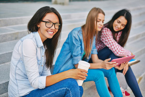 Portrait Of Pretty Teenage Girl Looking At Camera With Her Friends On Background