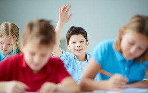 Portrait Of Smiling Schoolboy Raising Hand At Workplace With Classmates Near By