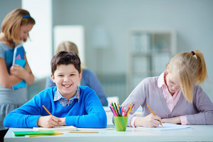 Portrait Of Happy Schoolboy At Workplace Looking At Camera On Drawing Lesson