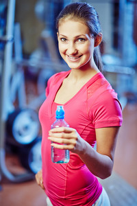 Happy Young Woman With Bottle Of Water Looking At Camera