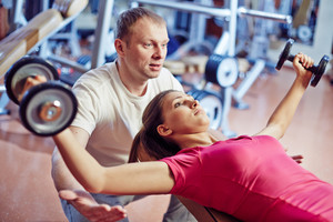 Portrait Of Pretty Girl Training In Gym With Her Trainer Helping Her