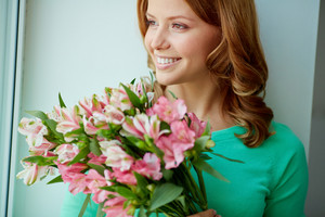 Portrait Of Smiling Female With Bunch Of Pink Flowers