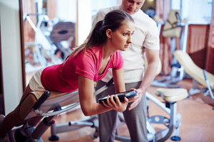 Sportive Girl Training In Gym With Her Trainer Near By