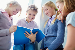 Portrait Of Three Happy Schoolgirls Looking At Notes In Exercise Book Held By Schoolboy