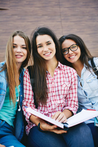 Company Of Happy Teen Girls With Open Book Looking At Camera Outside