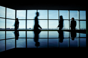 Silhouettes Of Several Office Workers On Background Of Window